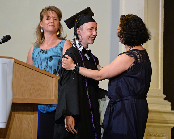 RYAN HUTTON/ Staff photo<br /> New Liberty Innovation School graduate Kaeden Brown receives a diploma and a hug from teacher Jenni Clock at the school's graduation ceremony at the Salem YMCA's Ames Hall on Thursday