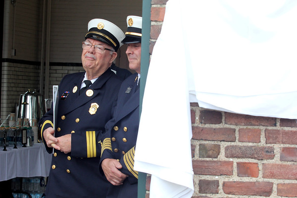 AMY SWEENEY/Staff photo. Rev. Norman LaPointe, left, and Chief David Cody listen as Salem Mayor Kim Driscoll speaks on half of the city during the dedication the fire station on Loring Ave to Joseph A. O'Keefe, Sr.  O'Keefe, a beloved city official who died in September 2015. He had a long and celebrated tenure on City Council. O'Keefe also served as state fire marshal from 1977 to 1992.