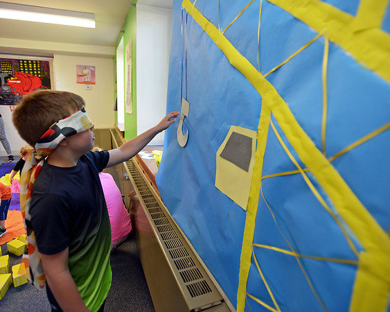 """RYAN HUTTON/ Staff photo<br /> Jacob Diefenbach, 9, plays a game of """"pin the hook on the crane"""" at the Salem Public Library's kid's summer reading program kick off party on Wednesday."""