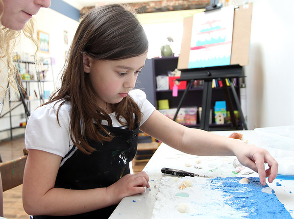 Six-year-old Peyton Tibert, of Danvers, carefully places a piece of sea glass on her Florida waves sand art project on Tuesday afternoon at Let's Get Creative in Beverly during an after school art class. DAVID LE/Staff photo