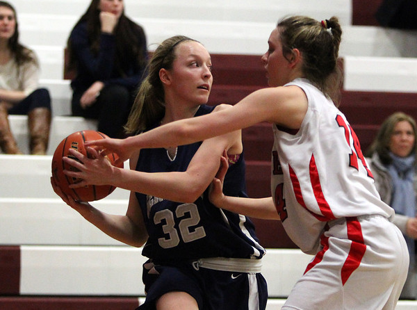 Hamilton-Wenham's Catherine Ecker (32) looks to pass while being defended by Watertown's Gianna Copolla (14) on Thursday evening in the D2 North Semifinal at Chelmsford High School. DAVID LE/Staff photo 3/6/14