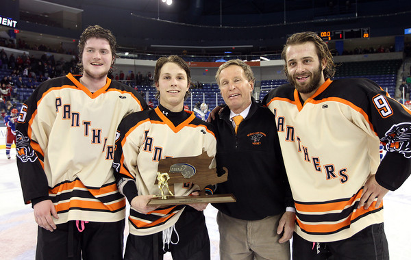 From left, Beverly senior captain Sean Munzing, Connor Irving, Head Coach Bob Gilligan, and senior captain Matt Hamor with the D2 North Championship trophy after Beverly dominated Tewksbury 9-1. The Panthers advance to the D2 State Final to be played next Sunday at the TD Garden where the Panthers will take on South Division Champion Medfield. DAVID LE/Staff photo 3/10/14