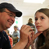 Jim Silva, of Hamilton, smiles while painting a Cat in the Hat on nine-year-old Chloe Conley, of Ipswich, at the Green Eggs and Ham Breakfast held by the Kiwanis Club at the Italian Community Center in Beverly on Saturday morning. DAVID LE/Staff photo 3/29/14