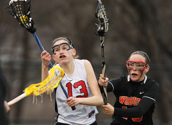 Marblehead sophomore Corinne Mayle (13) controls the ball while being pursued closely by a Woburn player on Friday afternoon. DAVID LE/Staff photo 3/28/14