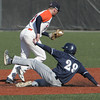 Ken Yuszkus/Staff photo: Salem: Salem State University's Ryan Beliveau had tagged second base for an out and passes Brandeis' Brian Allen who is sliding into second during the Brandeis at Salem State University baseball game.