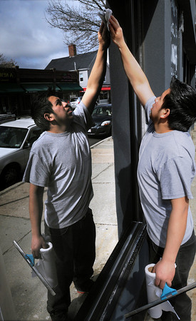 Ken Yuszkus/Staff photo: Beverly:   Nolbel De Leon washes the windows at Soma restaurant on Cabot Street in Beverly in his t shirt on the 1st day of spring.
