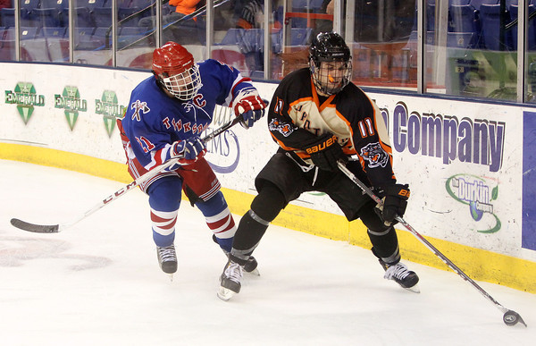 Beverly senior forward Ryan Santo (11) controls the puck behind the Tewksbury net while being chased by Tewksbury senior captain Jeff Giasullo (21) during the D2 North Final at the Tsongas Center at UMass Lowell on Monday evening. Beverly dominated Tewksbury 9-1 to advance to the D2 State Final to be played next Sunday at the TD Garden where the Panthers will take on South Division Champion Medfield. DAVID LE/Staff photo 3/10/14