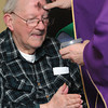 Ken Yuszkus/Staff photo: Resident Robert Martin has the sign of the cross drawn with ashes on his forehead by Father Shawn Carey at the New England Homes for the Deaf on Ash Wednesday.