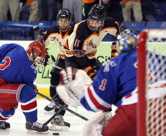 Beverly junior forward Jesse MacLaughlin (15) digs for a puck in the skates of Tewksbury senior captain Ross Budryk (2) during the D2 North Final at the Tsongas Center at UMass Lowell on Monday evening. Beverly dominated Tewksbury 9-1 to advance to the D2 State Final to be played next Sunday at the TD Garden where the Panthers will take on South Division Champion Medfield. DAVID LE/Staff photo 3/10/14