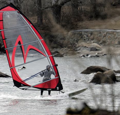Ken Yuszkus/Staff photo:  Beverly: Dave Winslow comes ashore at Lynch Park after windsurfing in Salem Harbor on a windy Friday afternoon.