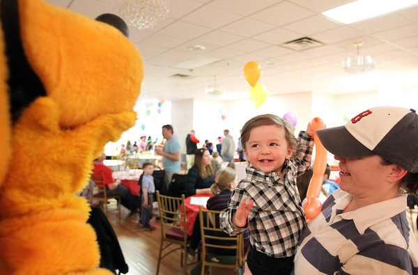 One-year-old Sawyer LaVita, of Peabody, smiles after seeing Pluto, while being held by his mother Teresa, at the Green Eggs and Ham Breakfast held by the Kiwanis Club at the Italian Community Center in Beverly on Saturday morning. DAVID LE/Staff photo 3/29/14