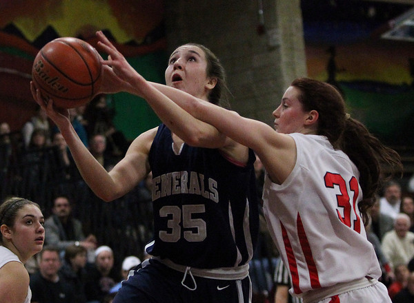 Hamilton-Wenham senior captain Sam Charette (35) goes up strong for a layup while being fouled by Watertown's Katelyn Rourke (31) during the second period of play on Thursday evening. DAVID LE/Staff photo 3/6/14