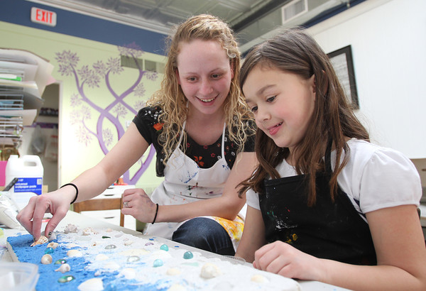 Six-year-old Peyton Tibert, of Danvers, right, with help from Let's Get Creative Art Director Emily Pallin, smiles as she looks over her Florida waves sand art project on Tuesday afternoon during an after school art class. DAVID LE/Staff photo
