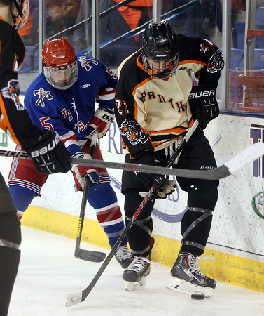 Beverly senior forward Graham Doherty (21) tries to get control of puck in his skates while being pursued by Tewksbury junior forward Ryan Meade (5) during the D2 North Final at the Tsongas Center at UMass Lowell on Monday evening. DAVID LE/Staff photo 3/10/14
