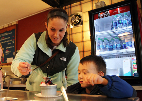 Casey King helps five-year-old Josh Stevens of Danvers put sprinkles on his ice cream sundae during an Ice Cream Social Fundraiser to benefit the Colleen Ritzer Memorial Fund held at Putnam Pantry Candies in Danvers on Saturday afternoon. DAVID LE/Staff photo 3/29/14