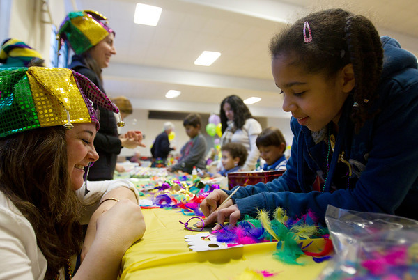 Gabrielle DaSilva, 10, of Peabody, right, chats with Stephanie Dalaire, also of Peabody, while making a Mardi Gras mask at St. Peter the Apostle Church's Mardi Gras Celebration on Tuesday evening. DAVID LE/Staff photo