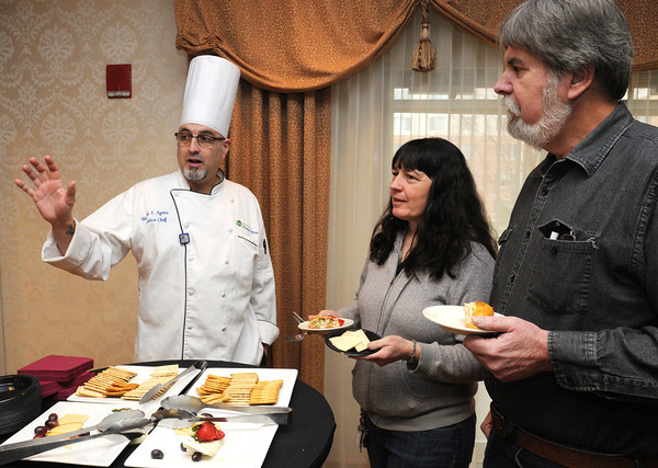 Ken Yuszkus/Staff photo: Peabody:  Michael Ayers, executive chef at Brooksby Village, speaks with Cheryl and Paul Doucette from Saugus during the Taste of Brooksby. Chefs prepared sample foods for visitors to try.