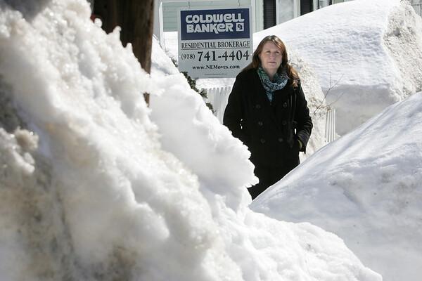 KEN YUSZKUS/Staff photo.  Coldwell Banker realtor Andrea Dodge stands amongst snowbanks at the house for sale at 39 Hathorne Street in Salem.   03/06/15