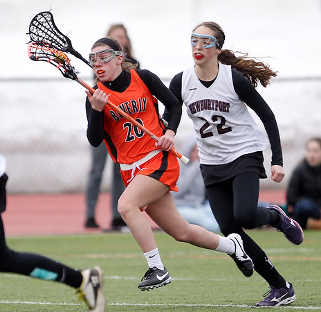 DAVID LE/Staff photo. 3/31/15. Beverly's Amanda Rosenberger (20) sprints the ball upfield while being pursued by Newburyport's Becca Turi (22).