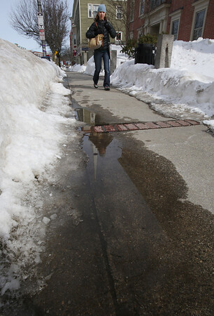 KEN YUSZKUS/Staff photo.  Susannah Bothe of Salem walks past a puddle caused by melting snow on Cabot Street in Beverly. Warm temperatures forcasted for Wednesday should continue to melt the snow.   03/03/15