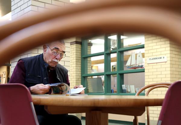 KEN YUSZKUS/Staff photo.      Bill Colella reads a book in a quite spot at the Peter A. Torigian Senior Center in Peabody.       03/14/16