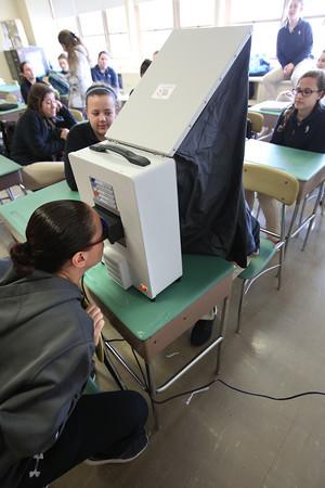 KEN YUSZKUS/Staff photo.      Health and wellness teacher Karen Guillemette, left, demonstrates the newly aquired Melanoma Facial Skin analysis machine at Bishop Fenwick High School.   03/29/16