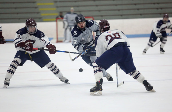 HADLEY GREEN/ Staff photo <br /> St. John's Justin Dalton (12) chases the puck while guarded by Belmont's Alec Morin (6) and Adam Cronin (22) during the St. John's Prep v. Belmont High Division 1 North MIAA playoff game at the Chelmsford Forum on Wednesday, March 1st, 2017.
