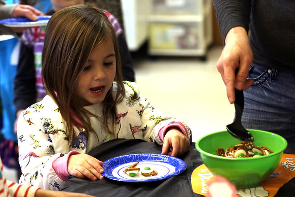 "HADLEY GREEN/ Staff photo <br /> Sydney Costanzo, 5, puts ""green eggs and ham"" pretzels on her plate at the Dr. Seuss birthday party at the Peabody Institution Library South Branch on Thursday, March 2nd, 2017."