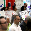 HADLEY GREEN/ Staff photo<br /> A group of people held signs in the back of the room to show their support for the passage of Salem's Sanctuary for Peace ordinance.