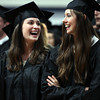 Gordon College graduates Erin Bousfield, left, and Rebecca Blizard, right, share a laugh prior to the start of the Commencement exercises on Saturday morning in the Bennett Center Gymnasium. DAVID LE/Staff photo. 5/18/14.