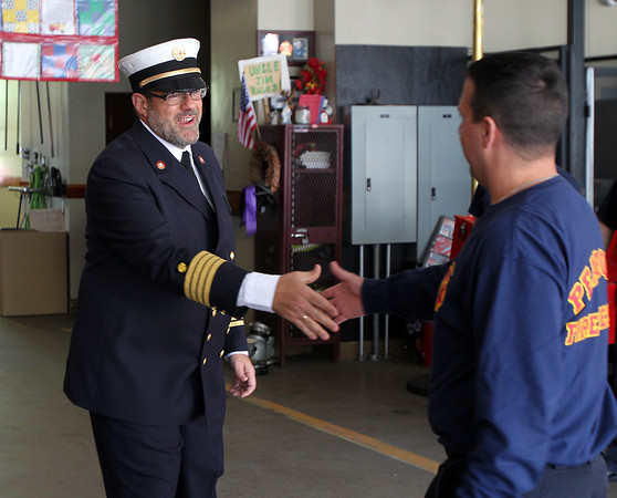 Father Chris Foustoukos, of St. Vasilios Greek Orthodox Church is being appointed as the Peabody Fire Department's full-time volunteer chaplain. He greets firefighter John Soares at the Peabody Fire House on Wednesday afternoon. DAVID LE/Staff photo. 5/14/14.