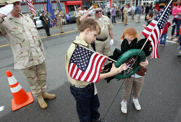 Twelve-year-old Robert Wolniewicz, left, and nine-year-old Michelle Mondi, right, place a wreath in Danvers square as Charles Gould, Commander of Legion Post 180 of Danvers, and Bruce Sweeter, Commander of VFW Post 2359, salute during the annual Danvers Memorial Day Parade. DAVID LE/Staff photo. 5/26/14.