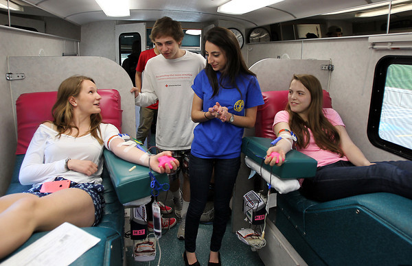 Hamilton-Wenham freshman Bryce Bucci and senior Rae Sanchez, center, check up on fellow students, junior Maddy Bukkhegyi, left, and senior Daisy Sears, as they donate blood on Friday morning. Rae Sanchez, is the sister of A.J. Sanchez, now 23, who was involved in a car accident back in 2003 and needed many units of blood to survive. The family has been running a blood drive in his honor for the past eight years at the high school. Sanchez, Bucci, and Bukkhegyi were in charge of running this year's blood drive. DAVID LE/Staff photo. 5/2/14