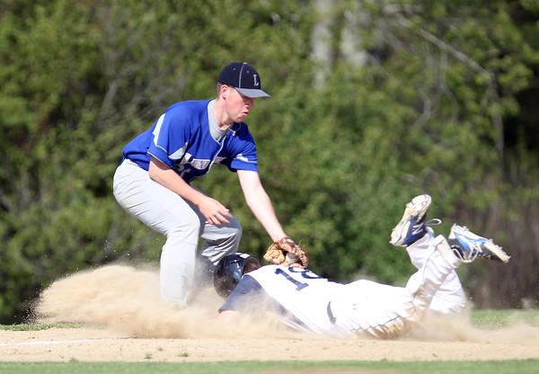 Pingree freshman Cameron Schmitt (18) slides safely into third base before Lexington Christian Academy third baseman Thomas Segreve can apply the tag. Schmitt tripled in two runs in the 1st inning. DAVID LE/Staff photo. 5/14/14.