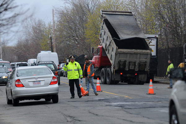 JIM VAIKNORAS/Staff photo A police officer directs traffic as worker patch Canal Street near Lyme Street in Salem.