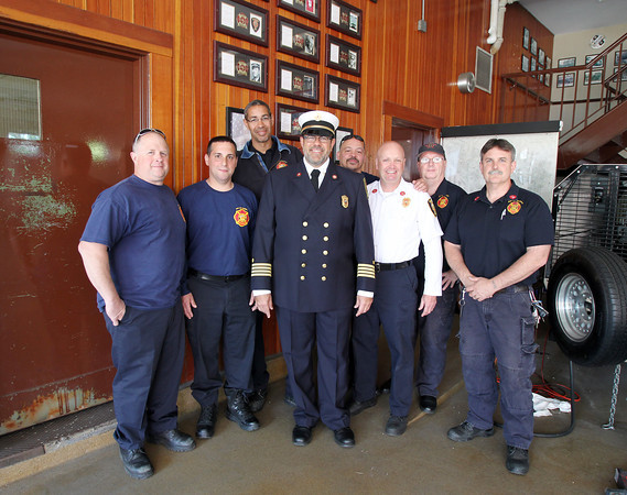From left, Bil Jacavanco, John Soares, Russ Lewis, Father Chris Foustoukos, Jimmy Kimber, Deputy Chief Rick Nelson, Tom Desmond, and Captain Ted Quinn inside the Peabody Fire Department. Father Chris Foustoukos, of St. Vasilios Greek Orthodox Church is being appointed as the Peabody Fire Department's full-time volunteer chaplain. DAVID LE/Staff photo. 5/14/14.