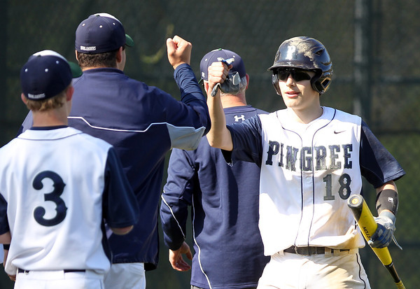 Pingree freshman Cameron Schmitt (18) gets a first bump from his teammates after he crossed the plate with the Highlanders 3rd run of the afternoon. DAVID LE/Staff photo. 5/14/14.