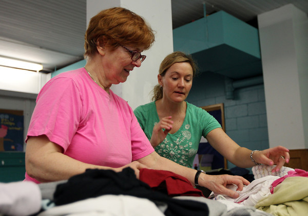 Mary Morrissey, of Salem, and Jenn Santo, co-Vice President of Parents United of Salem, sort through clothes donations made for those affected by the Dow St. fire which displaced 45 people. DAVID LE/Staff photo. 5/10/14