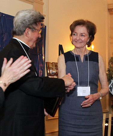 Father Louis Bourgeois, representing St. Anne's Parish of Salem, shakes hands with Anne Nigro, Chair of the Advisory Board of Catholic Charities North, after receiving the A Salute to Partnership award on Thursday evening at the Hawthorne Hotel during their annual Spring Gala. DAVID LE/Staff photo. 5/1/14