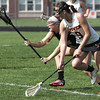 KEN YUSZKUS/Staff photo.  Bishop Fenwick's Caroline Crawford scoops up the ball and runs with Ipswich's Marley Henderson at her side during the Bishop Fenwick at Ipswich High girls lacrosse North Division 2 quarterfinal playoff game.  5/29/14.