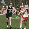 KEN YUSZKUS/Staff photo.  Ipswich's Meghan Collins carries the ball toward the net with Masco's Molly Gillespie at her side during the Ipswich at Masconomet girls lacrosse game. 5/12/14