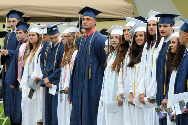 KEN YUSZKUS/Staff photo. Graduates stand during the processional while waiting until every graduate is in place at the Peabody Veterans Memorial High School graduation.   5/30/14.