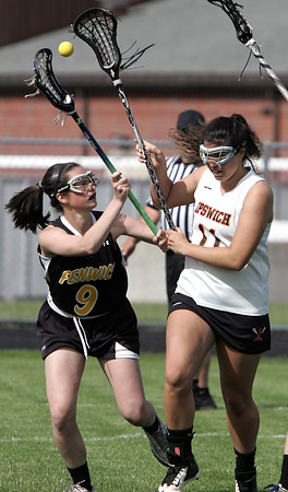 KEN YUSZKUS/Staff photo.  Bishop Fenwick's Ellen Fantozzi, left, and Ipswich's Olivia Moutevelis have a loose ball flying high during the Bishop Fenwick at Ipswich High girls lacrosse North Division 2 quarterfinal playoff game.  5/29/14.