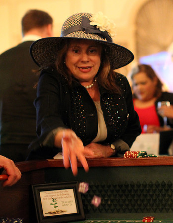 Linda Stark, of Salem, rolls the dice while playing craps at the 20th annual of the Hats Off to Education Fundraiser held on Friday evening at the Hawthorne Hotel. DAVID LE/Staff photo. 5/9/14.