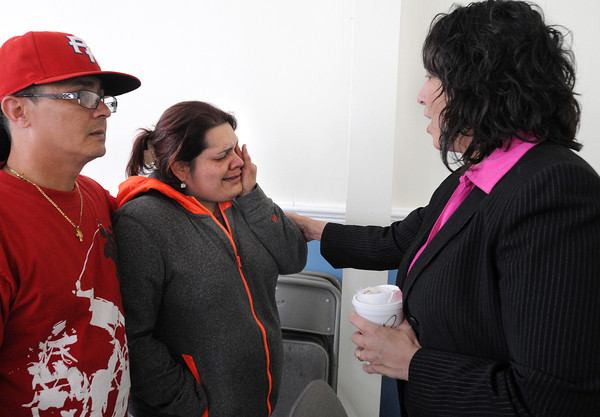 KEN YUSZKUS/Staff photo.  Xiomara Guman, center, who was displaced by the fire at 60 Dow Street in Salem speaks with Salem Mayor Kim Driscoll at the Salem Senior Center. Alexander Hernandez, left, is helping out his sister-in-law Xiomara Guman.