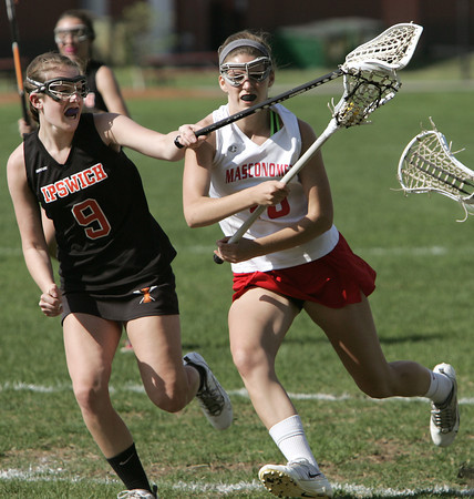 KEN YUSZKUS/Staff photo.  Ipswich's Marley Henderson, left, swats at the ball that Masco's Grace Fahey has during the Ipswich at Masconomet girls lacrosse game. 5/12/14