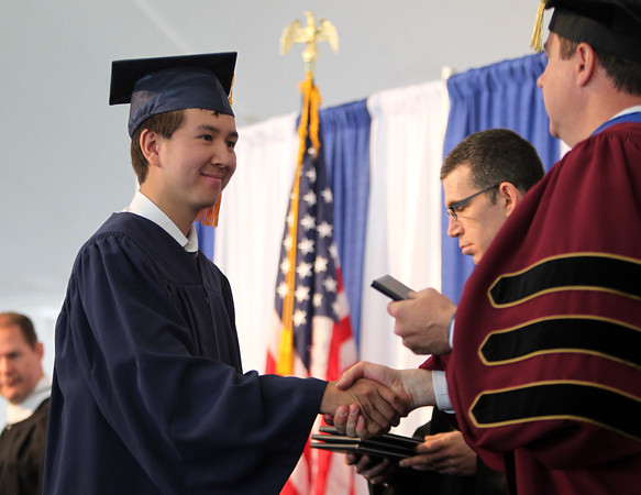 St. John's Prep graduate Rodney Bedell shakes hands with Headmaster Edward Hardiman while receiving his diploma during Commencement on Sunday afternoon at Ryken Field in Danvers. DAVID LE/Staff photo. 5/18/14.