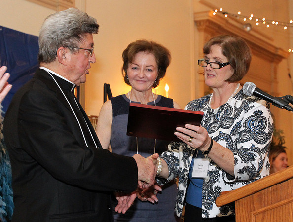 Father Louis Bourgeois, from St. Anne's Parish of Salem, left, accepts the A Salute to Partnership award from Deborah Kincade Rambo, right, President of the Catholic Charities of Boston, and Anne Nigro, Chair of the Advisory Board for the Catholic Charities North, on Thursday evening at the Hawthorne Hotel during their annual Spring Gala. DAVID LE/Staff photo. 5/1/14