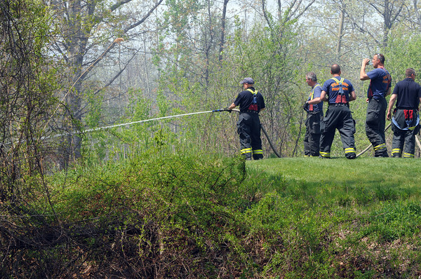 KEN YUSZKUS/Staff photo.  Firefighters work at controling the brush fire near the 14th tee at The Meadows golf course in Peabody .         5/12/14