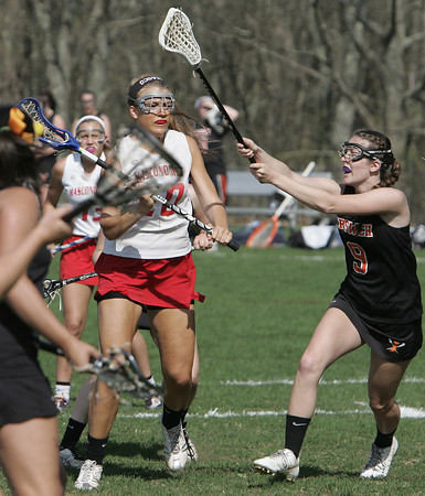 KEN YUSZKUS/Staff photo.  Ipswich's Marley Henderson, right swings at the ball before Masco's Sarah Yeakel lets loose to score a goal during the Ipswich at Masconomet girls lacrosse game. 5/12/14
